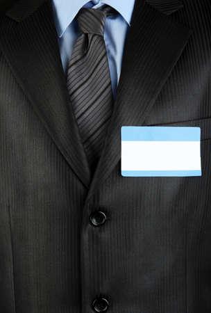 Blank nametag on businessmans black suit close up photo