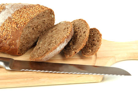 Bread with sesame seeds and knife on wooden board close up photo