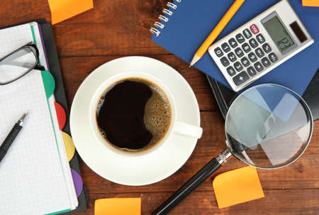 Cup of coffee on worktable covered with documents close up photo