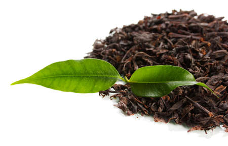 Dry black tea with green leaves, isolated on white photo