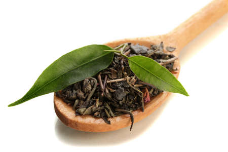Dry tea with green leaves in wooden spoon, isolated on white photo