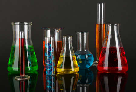 Test tubes with colorful liquids on dark grey background photo