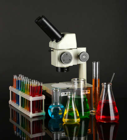 Test tubes with colorful liquids and microscope on dark grey background photo