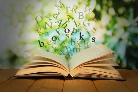 libros volando: Libro abierto con las letras que vuelan fuera de ella en el fondo brillante