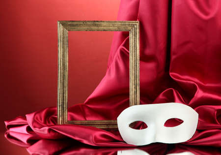 White mask, empty frame and golden silk fabric, on red background photo