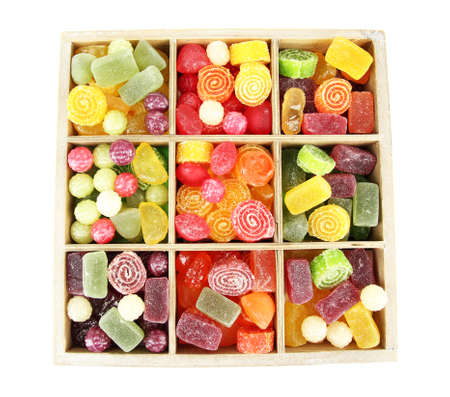 Multicolor candies in wooden box, isolated on white photo