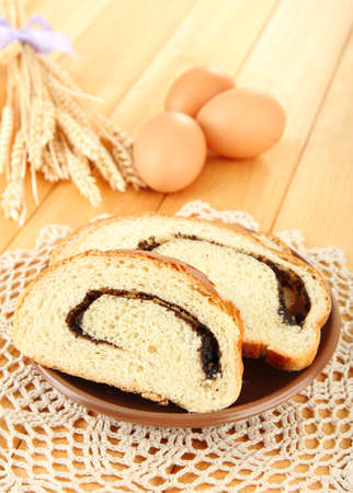 Loaf with poppy seeds on color plate, on wooden background Stock Photo - 18041585