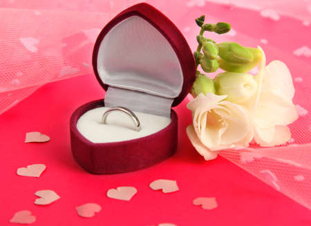 Beautiful box with wedding ring and flower on pink background photo