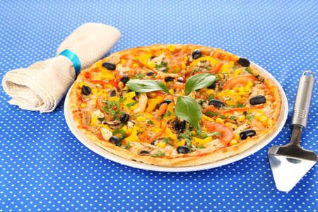 Tasty pizza on blue tablecloth close-up Stock Photo - 18041684