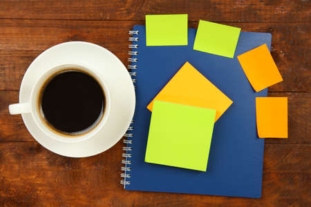 note book: Cup of coffee on worktable close up
