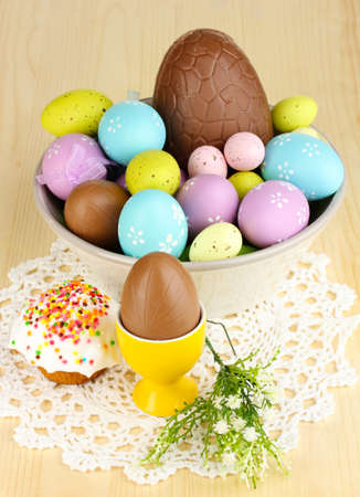 Composition of Easter and chocolate eggs and simnel on wooden table close-up photo