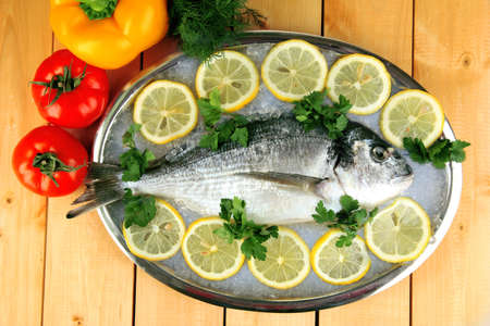 Fresh fish of dorado on tray with lemon and parsley on wooden table Stock Photo - 18043206
