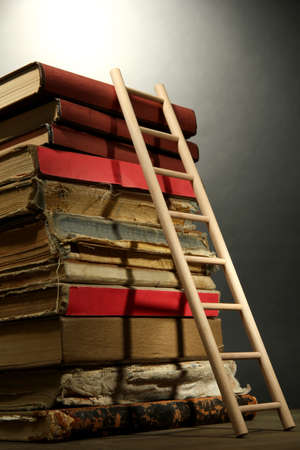 Old books and wooden ladder, on grey background photo
