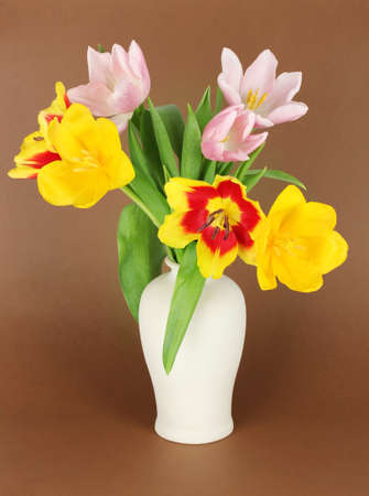 Beautiful tulips in bucket on brown background photo
