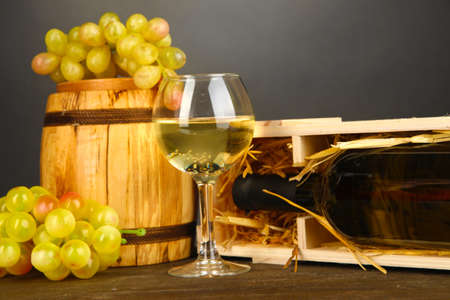 bordeau: Wooden case with wine bottle, barrel, wineglass and grape on wooden table on grey background Stock Photo