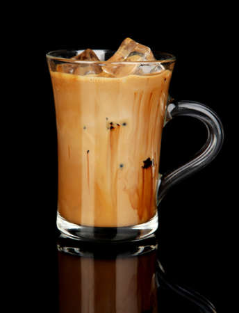 Cold coffee with ice in glass isolated on black photo