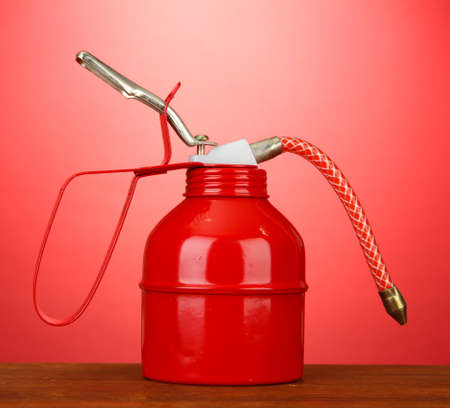 Oil can on red background Stock Photo - 18072268