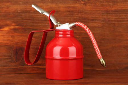 Oil can on wooden background photo