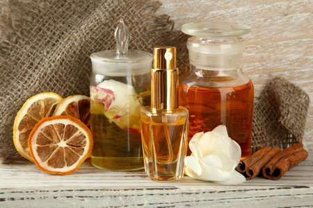 Bottles with ingredients for the perfume on wooden background photo