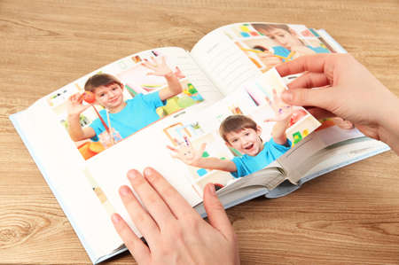 Photos in hands and photo album on wooden table Stock Photo - 19359496