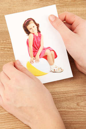 Photos in hands on wooden table Stock Photo - 19359507