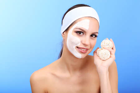 Young woman with clay facial mask, on blue background photo