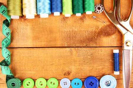 snip: Sewing accessories and fabric on wooden table close-up Stock Photo