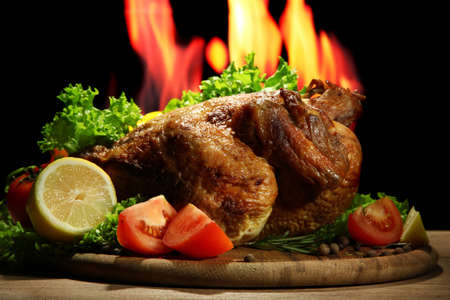 Whole roasted chicken with vegetables on plate, on flame background photo