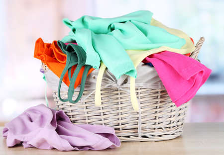 Clothes in wooden basket on table in room Stock Photo - 18139093
