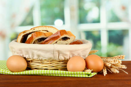 Loaf with poppy seed in wicker basket, on bright background photo