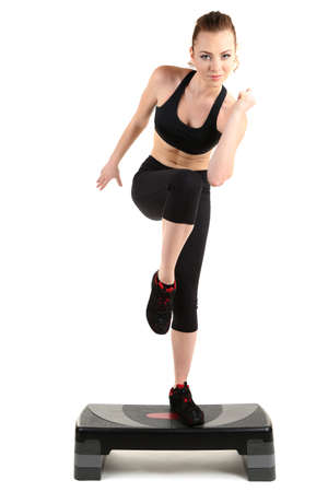 vigorous: Young woman doing fitness exercises on stepper isolated on white