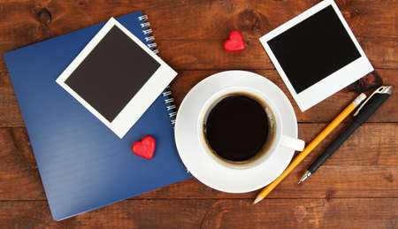 Cup of coffee on worktable covered with photo frames close up photo