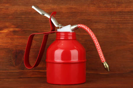 lubricator: Oil can on wooden background