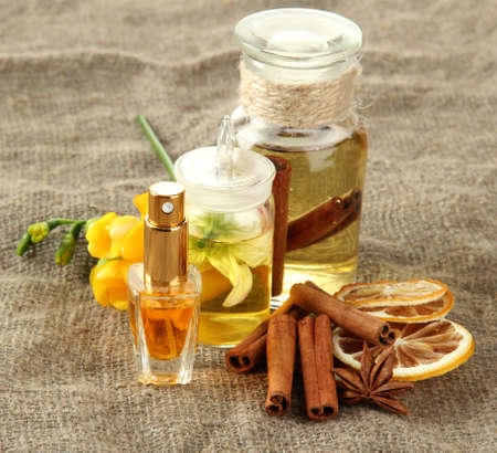 Bottles with ingredients for the perfume on burlap background photo