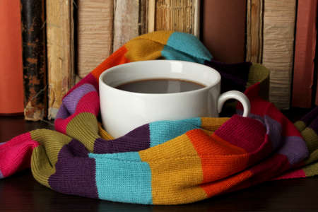 cold weather: Cup of coffee wrapped in scarf on books background