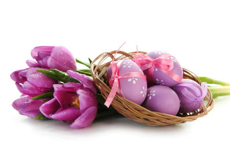 Bright easter eggs in basket and tulips, isolated on white photo
