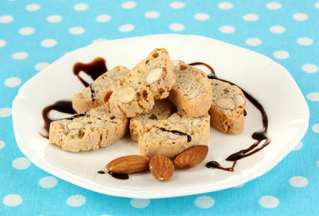 Aromatic cookies cantuccini on plate on blue tablecloth close-up photo