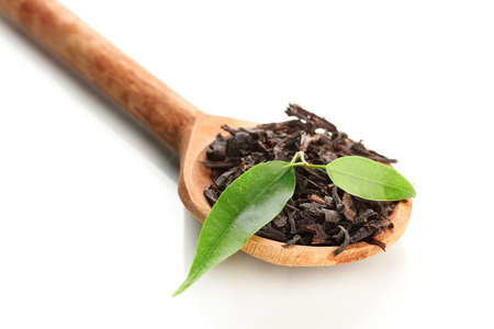 Dry black tea with green leaves in wooden spoon, isolated on white photo