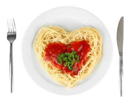 Cooked spaghetti carefully arranged in  heart shape and topped with tomato sauce, isolated on white photo