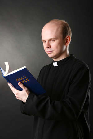 Priest with Holly Bible on black background photo