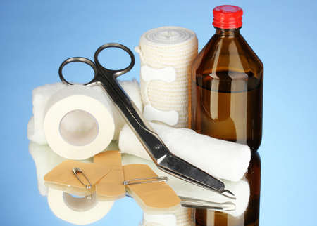 First aid kit for bandaging on blue background photo