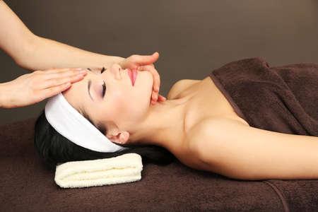Beautiful young woman in spa salon taking head massage, on dark background photo