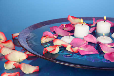 Rose petals and candles in water in vase on blue background close-up Stock Photo - 18301208