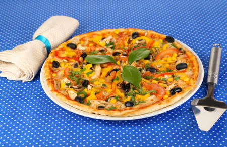 Tasty pizza on blue tablecloth close-up Stock Photo - 18301376