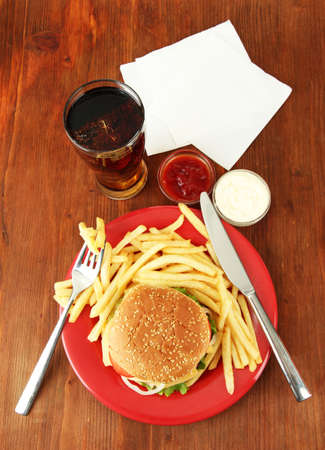 Tasty cheeseburger with fried potatoes and cold drink, on wooden background photo