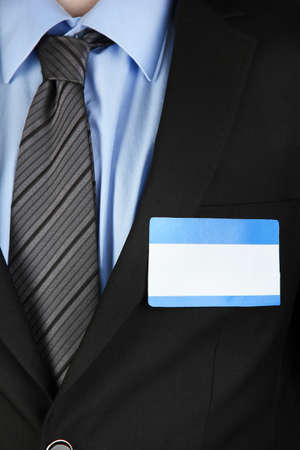 nametag: Blank nametag on businessmans black suit close up Stock Photo