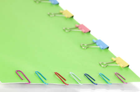 Green paper with binder and paper clips  close up photo