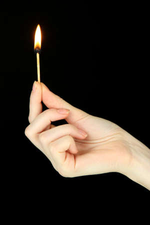 Burning lighter in female hand, isolated on black photo