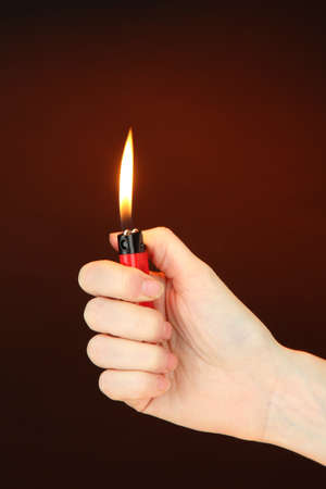 Burning lighter in female hand, on dark brown background Stock Photo - 18316133
