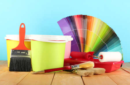 refurbishing: Paint pots, paintbrushes and coloured swatches on wooden table on blue background
